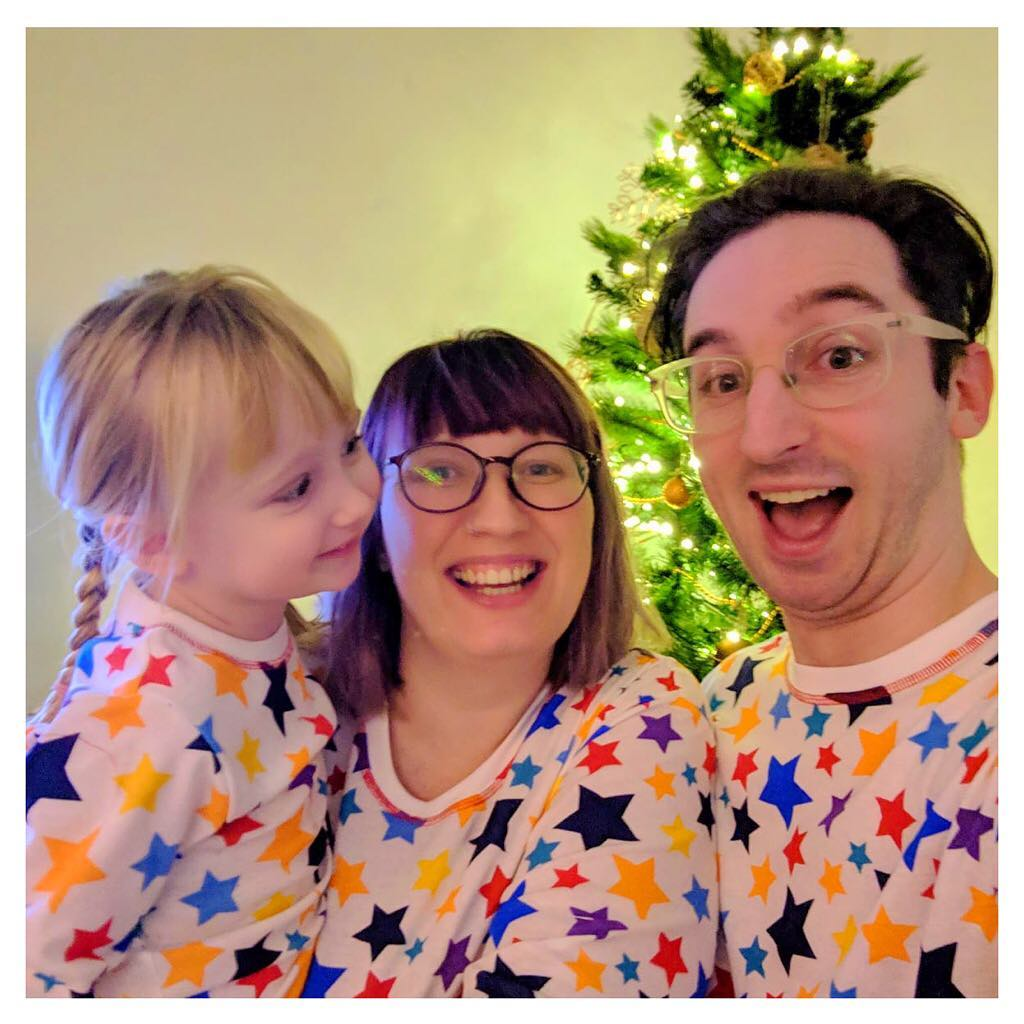 Christmas matching pjs in front of the christmas tree
