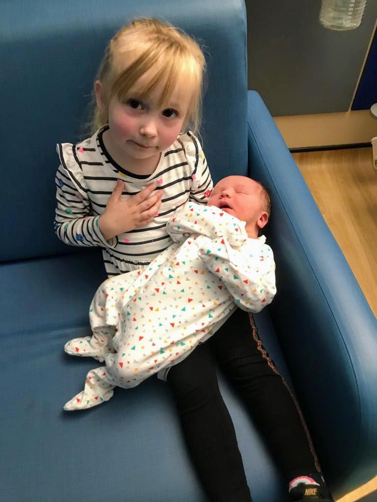 Cece holding newborn Rory at hospital