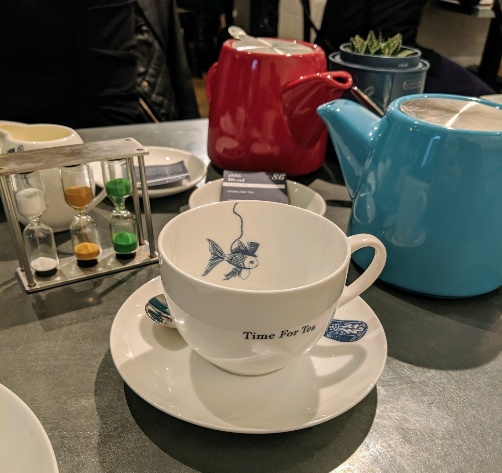 A cup that reads time for tea and a blue teapot