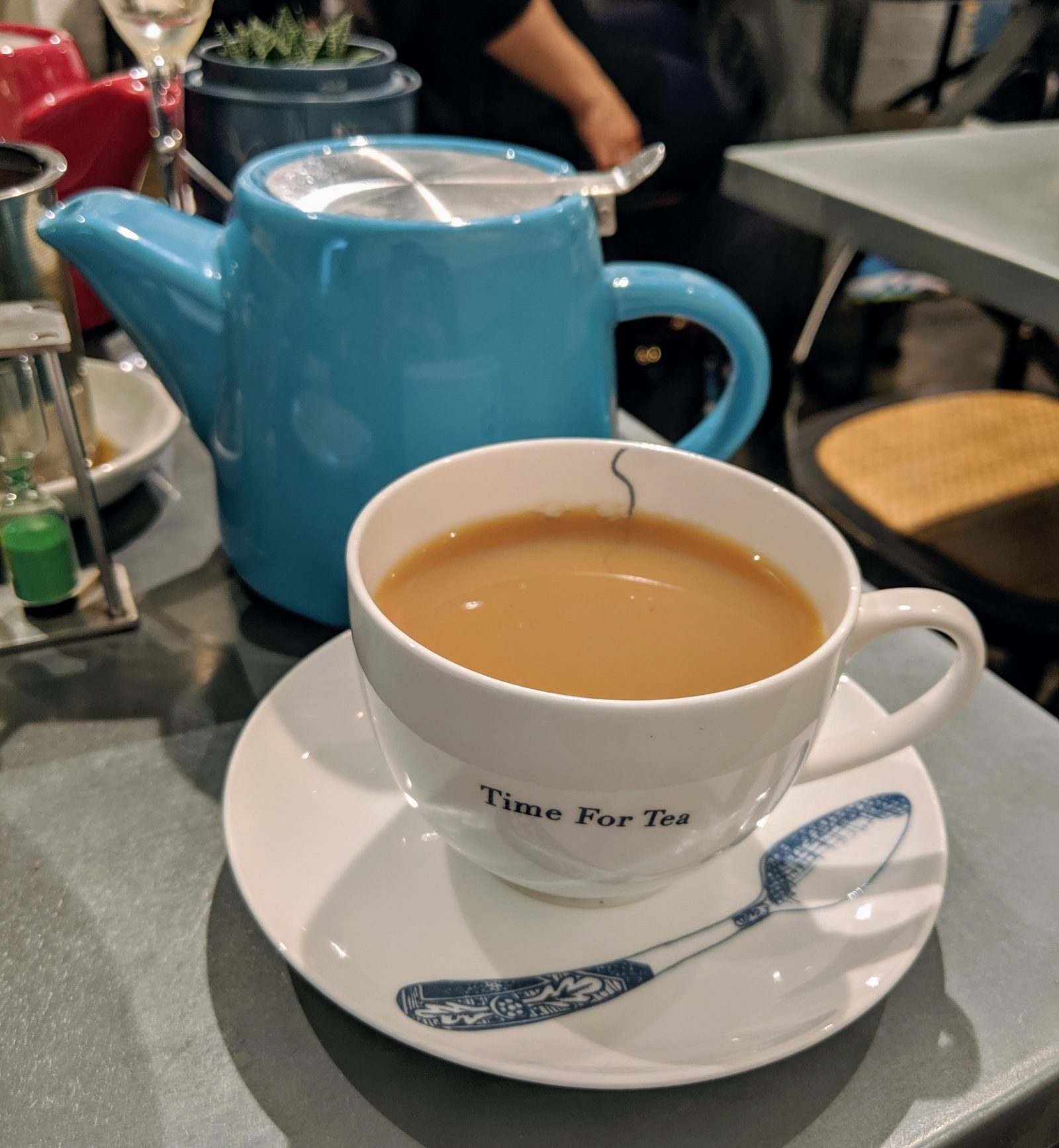 A warm cup of tea and a blue teapot