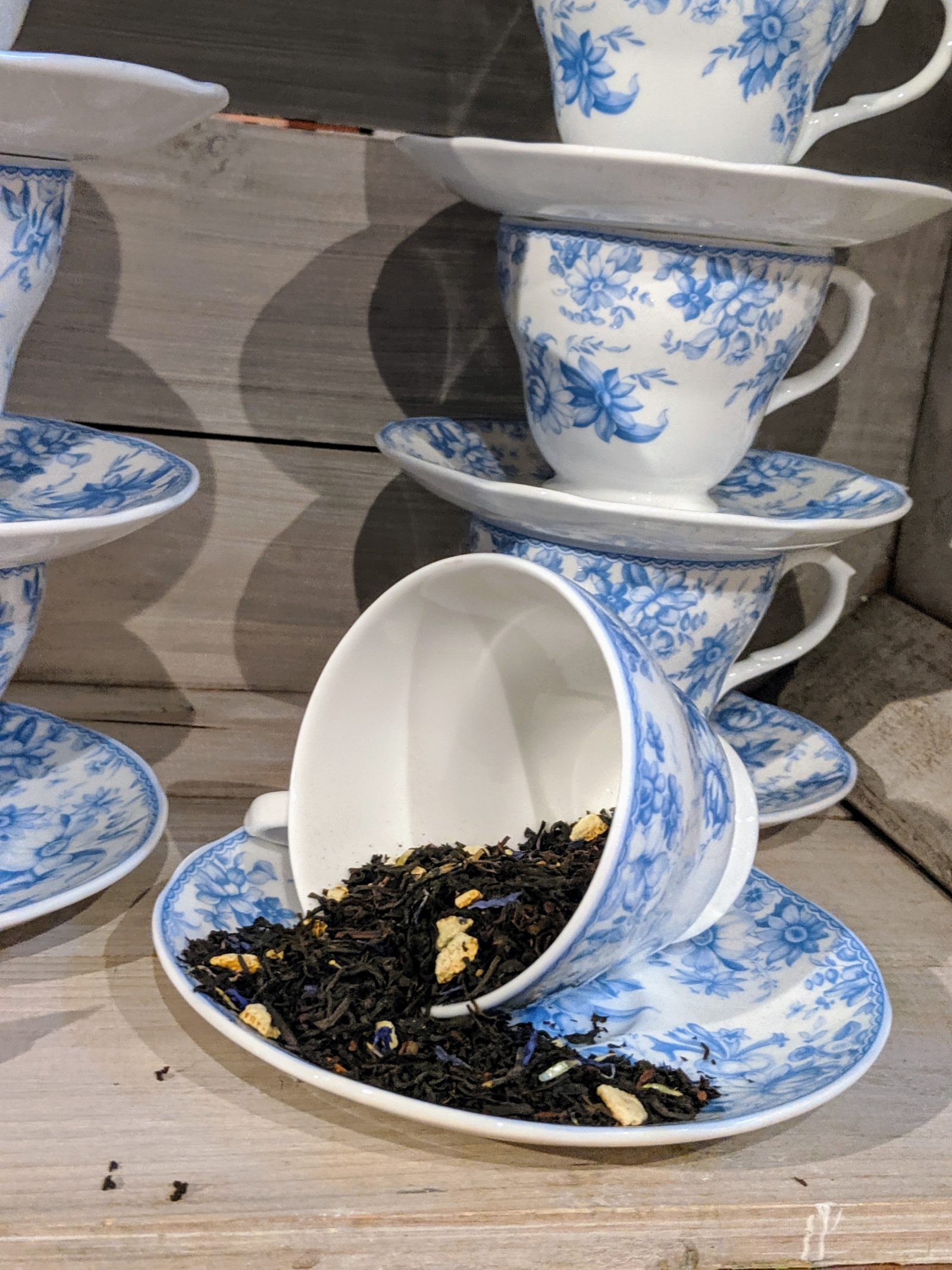 A tipped over blue and white teacup full of tealeaves