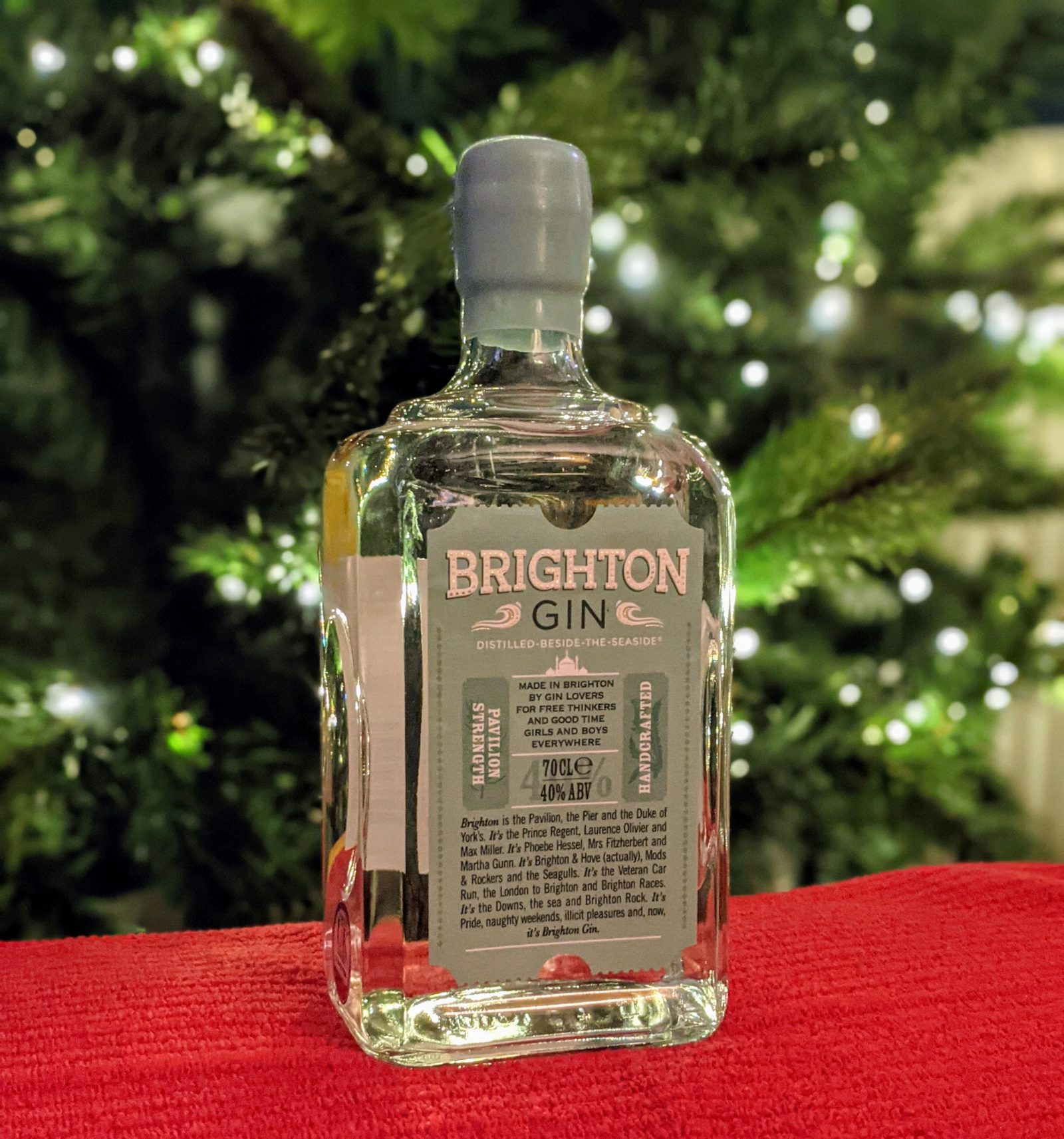 A bottle of Brighton gin in front of a lit Christmas tree