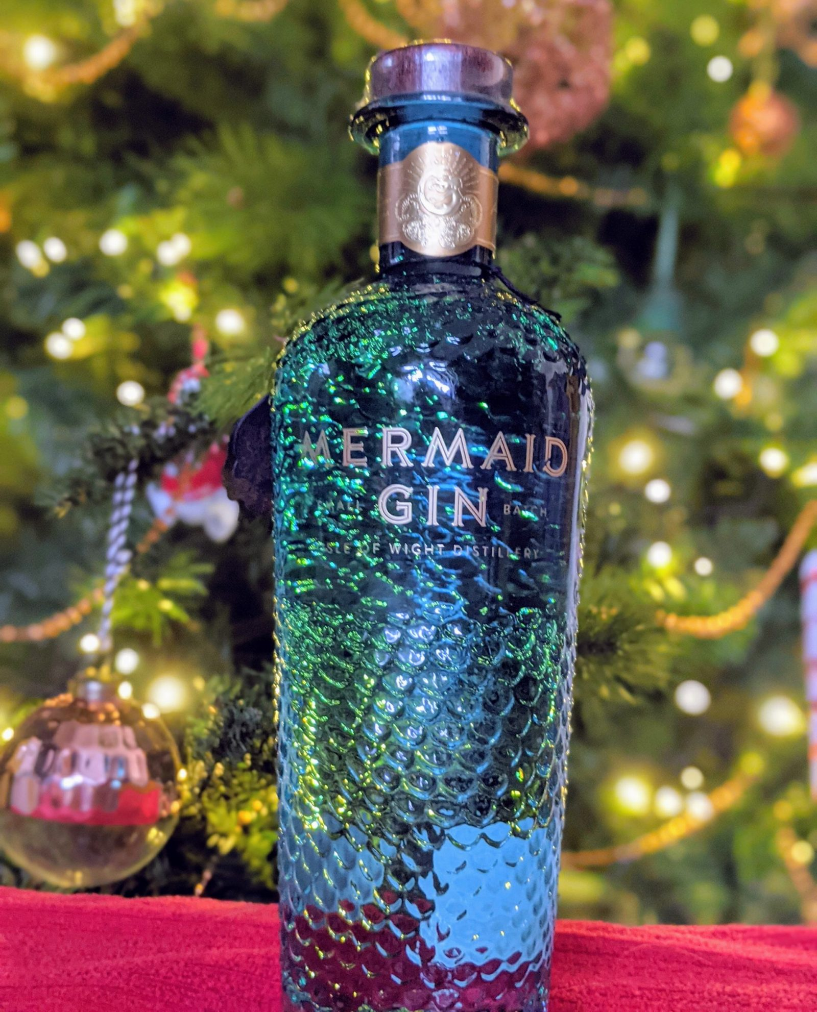 A bottle of Mermaid Gin in front of a Christmas tree
