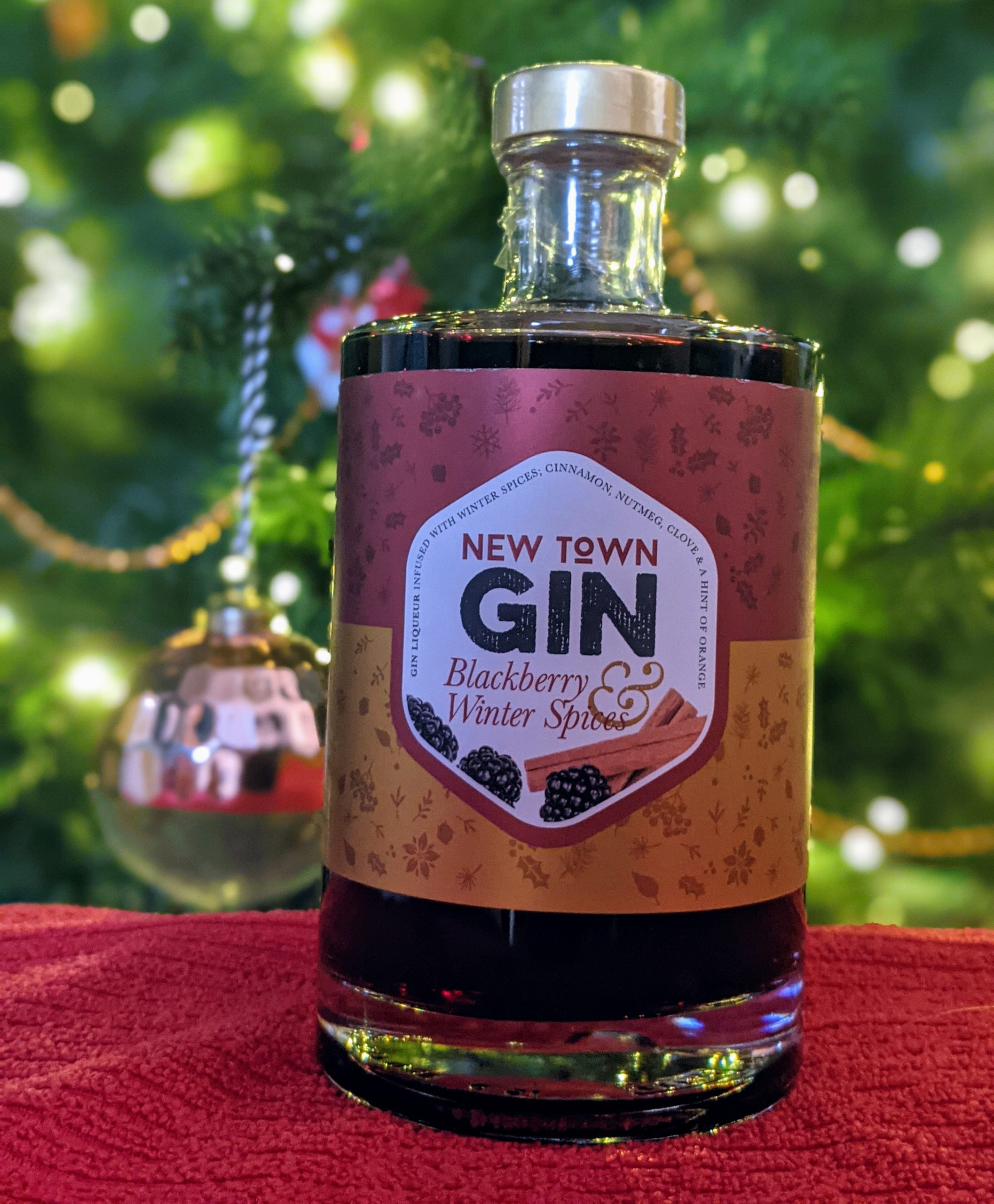 A bottle of New Town Gin Blackberry and Winter Spice Liquer in front of a Christmas tree